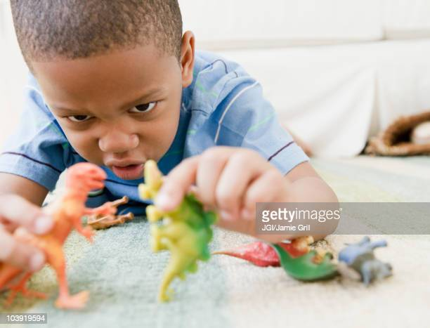 African American boy laying on floor playing with toy dinosaurs