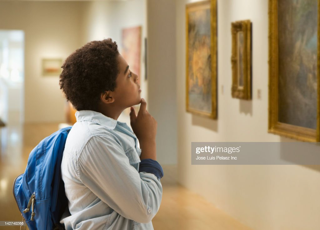 African American boy looking at painting in museum : Stock Photo