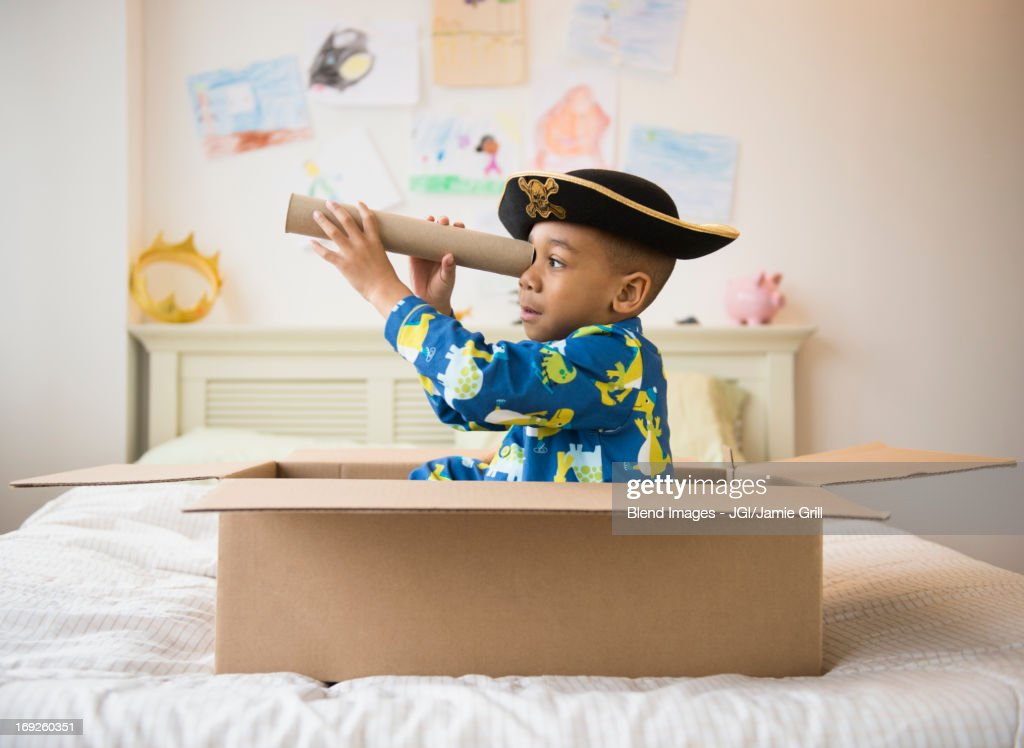 African American boy playing in cardboard box : Stock Photo