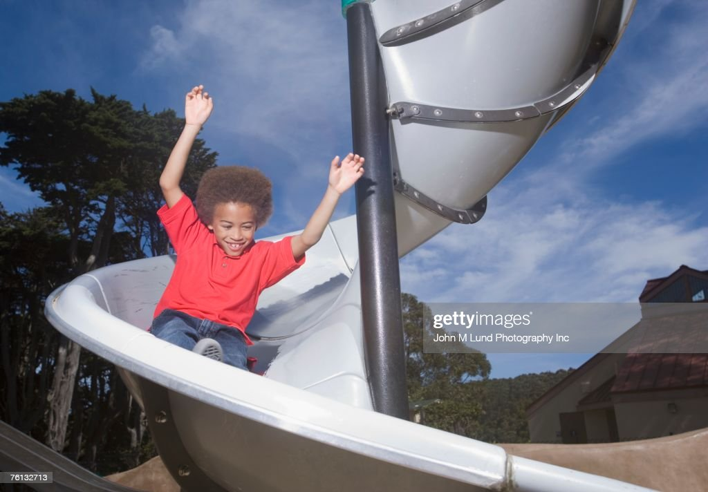 African American boy playing on slide : Stock Photo