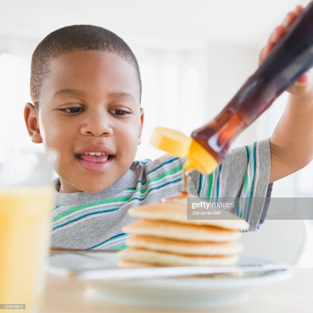 African American boy pouring syrup on pancakes : Stock Photo
