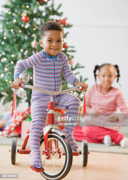 African American boy riding tricycle near Christmas tree