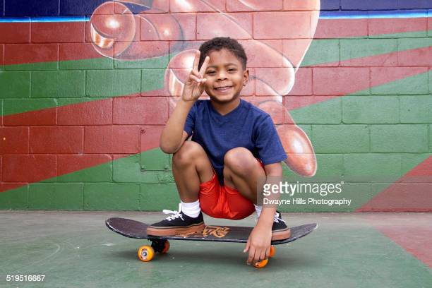 African American boy sitting on skateboard by urban mural