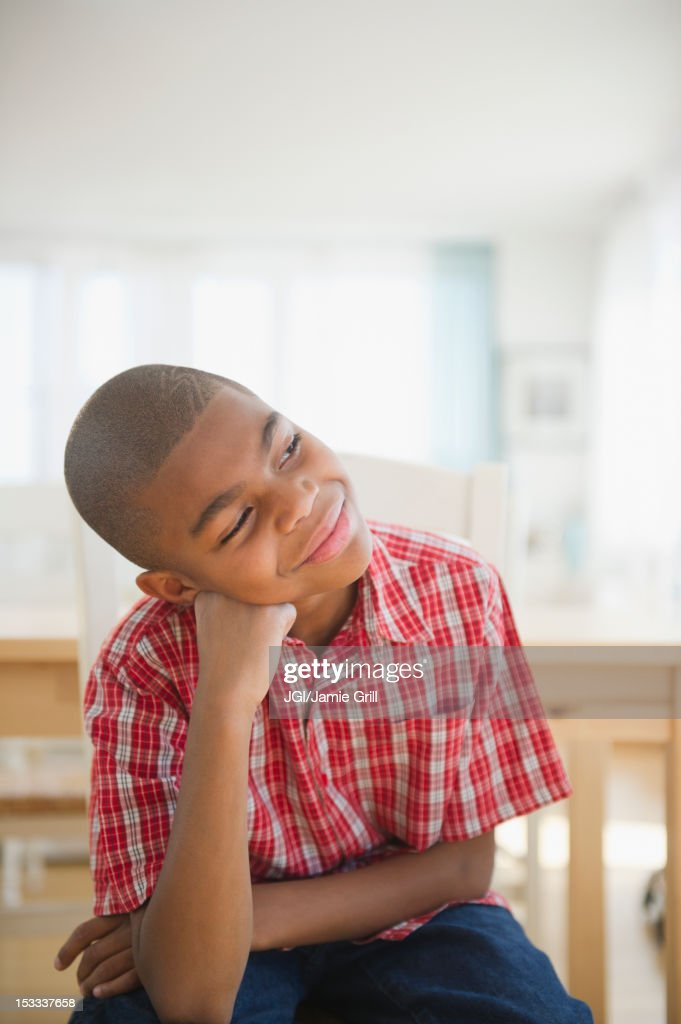 African American boy sitting with head in hands thinking : Stock Photo