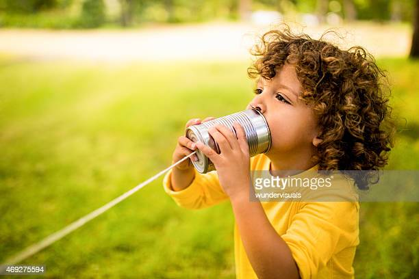 African American boy talking into tin can phone in park