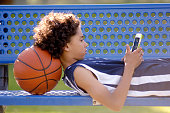 Ten year old African American boy sitting on a blue park bench outdoors, with a basketball, and texting on a mobile tablet.