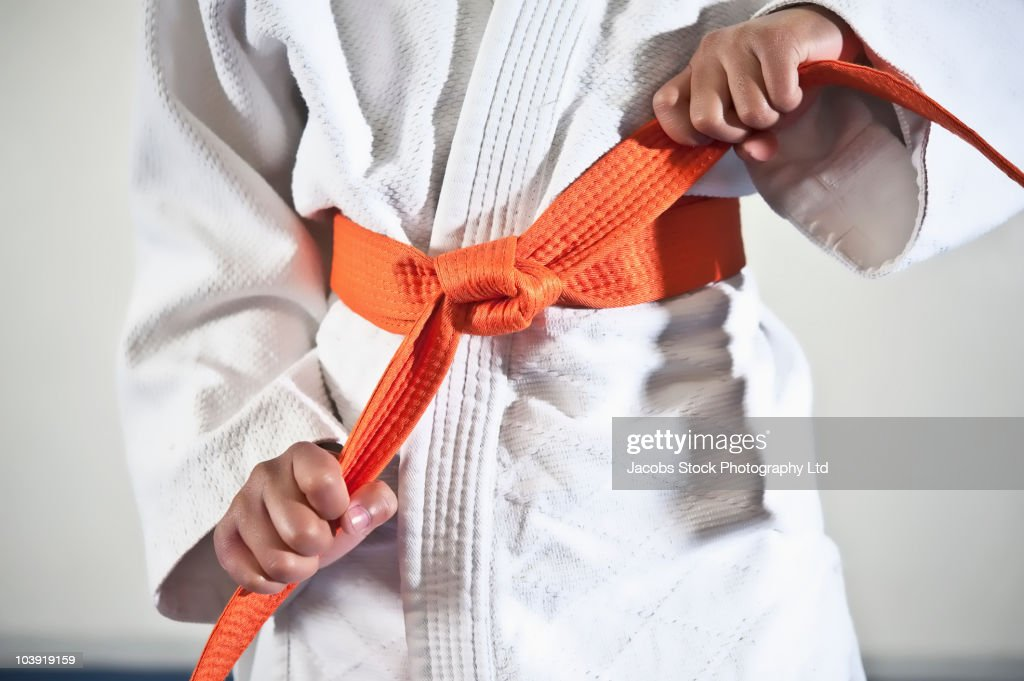 African American boy tightening karate belt : Stock Photo