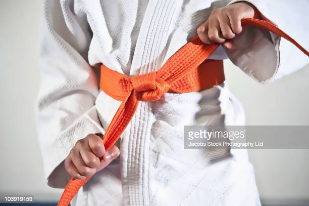 African American boy tightening karate belt