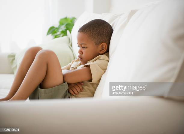 African American boy unhappy on sofa