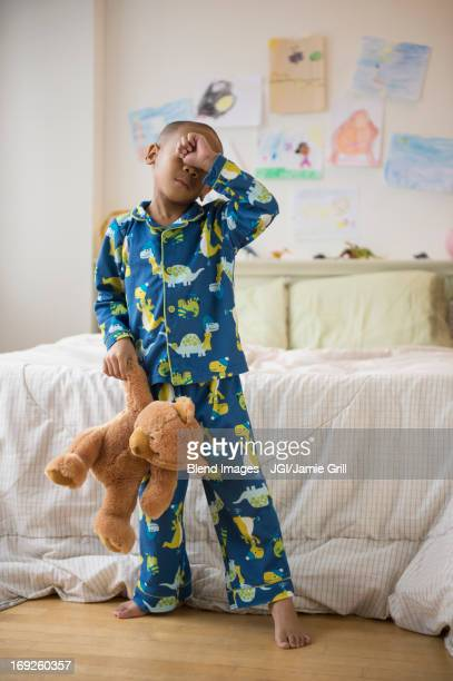 African American boy waking up in bedroom