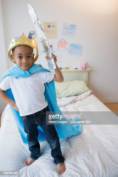 African American boy wearing costume on bed