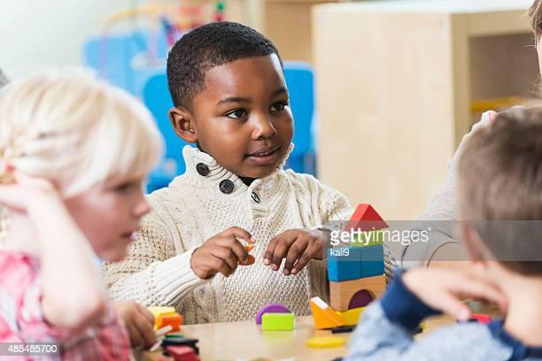 African American boy con amigos y bloques de construcción