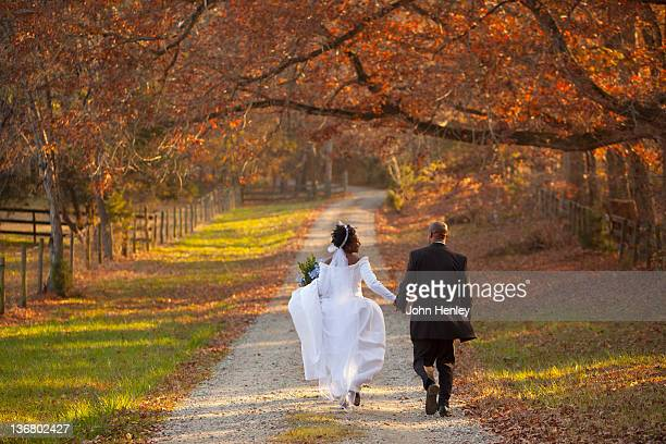 African American bride and groom walking on path