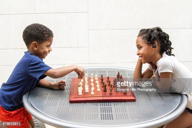 African American brother and sister playing chess