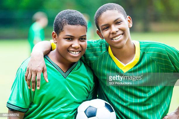 African American brothers smile after their soccer game