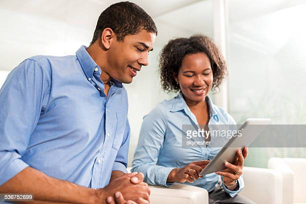African American business people using digital tablet.