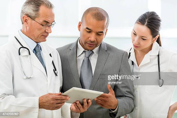 African American businessman and doctors using touchpad.