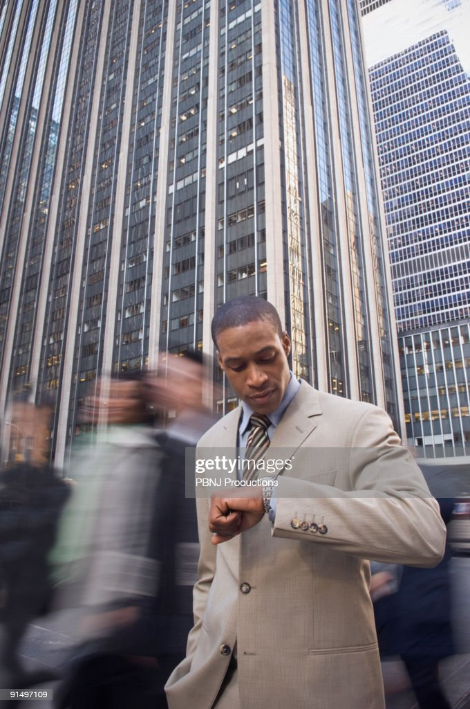African American businessman checking watch