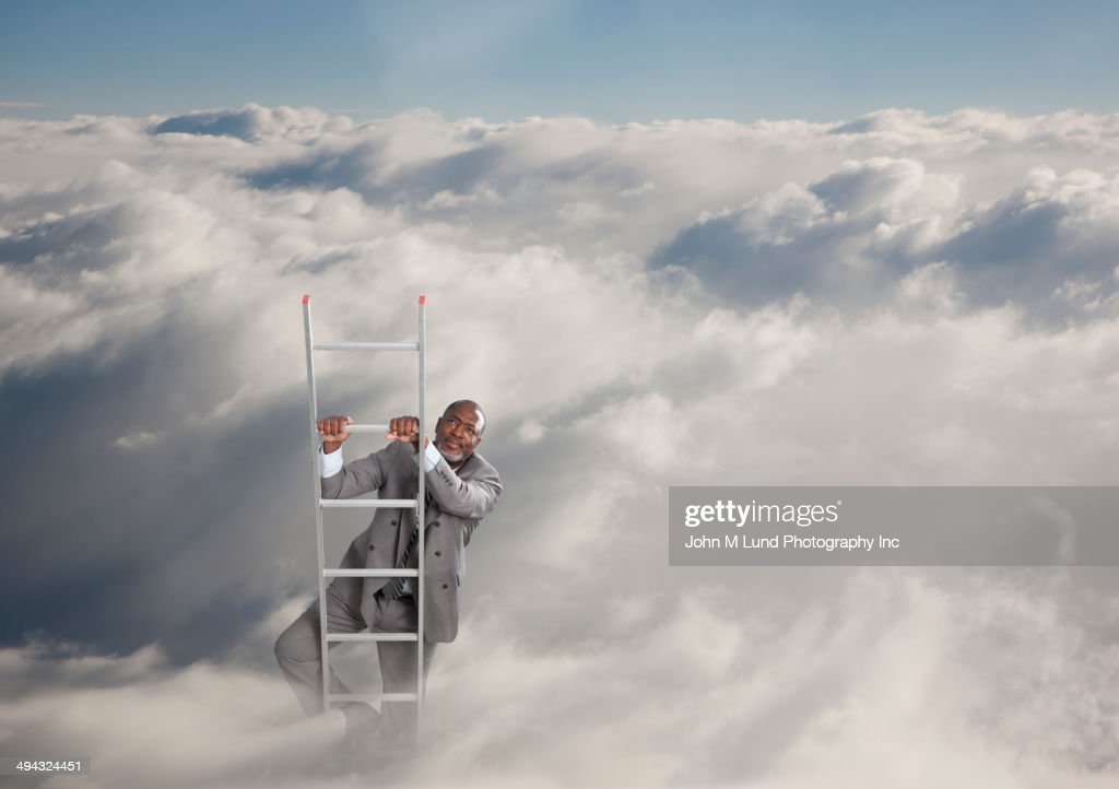 African American businessman climbing ladder in clouds