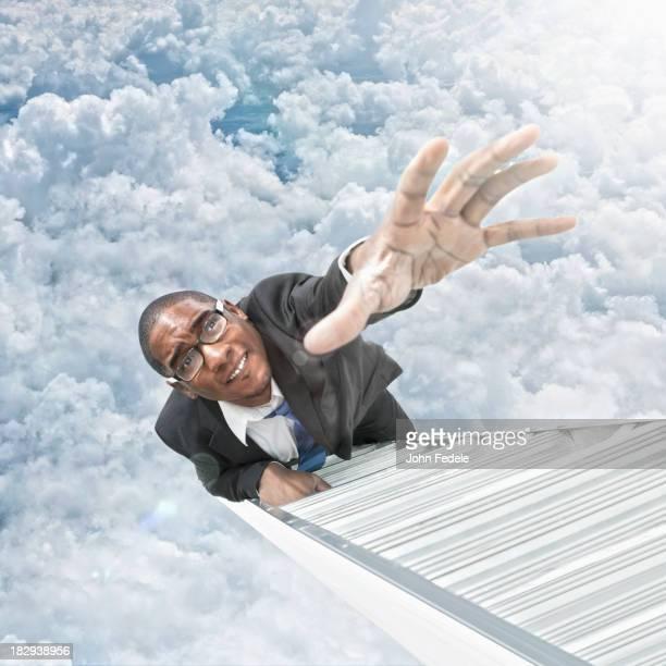 African American businessman climbing ladder
