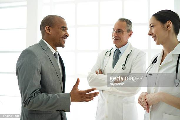 African American businessman communicating with doctors.