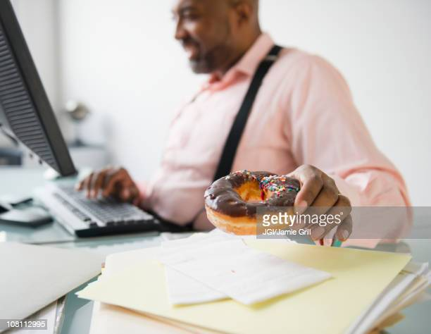African American businessman eating donut at desk
