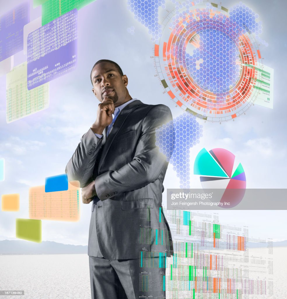 African American businessman examining illuminated holograms : Stock Photo