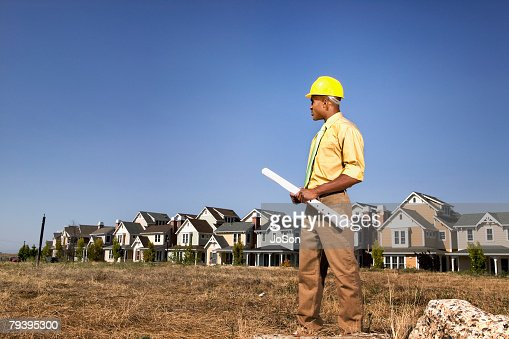 African American businessman holding blueprints : Stock Photo