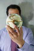 African American businessman holding globe in front of face