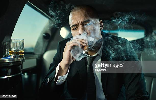 African American businessman in limousine smoking a cigar.