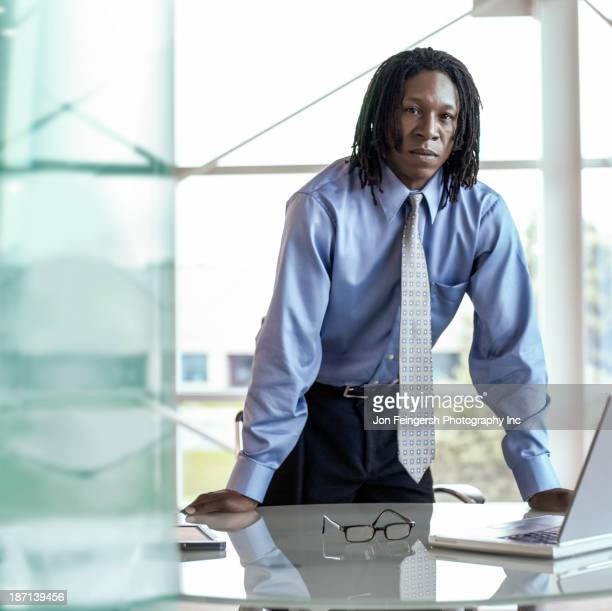 African American businessman leaning over desk