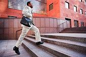 African American businessman running up steps