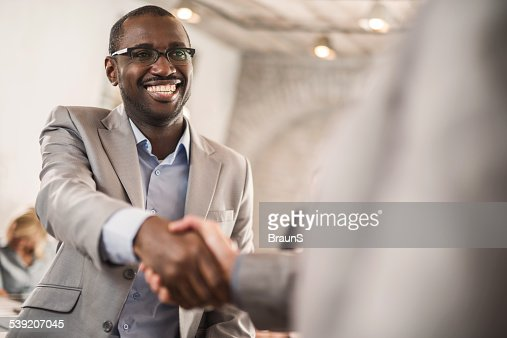 African American businessman shaking hands with his colleague.