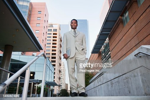 African American businessman standing at top of stairs : Stock Photo