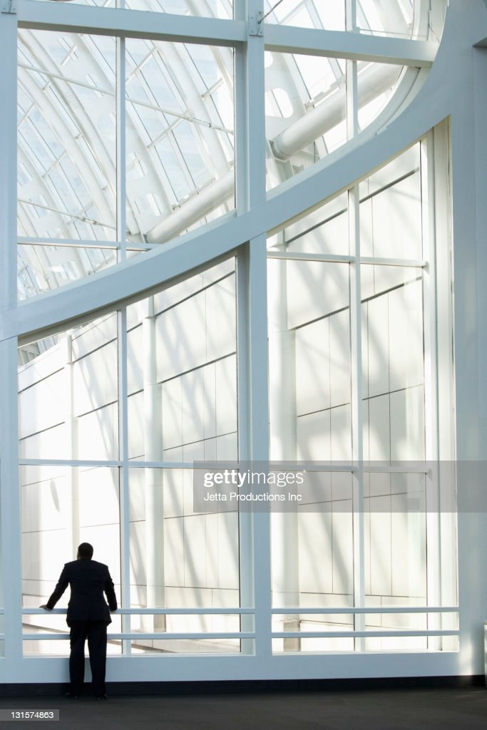 African American businessman standing in lobby : Stock Photo