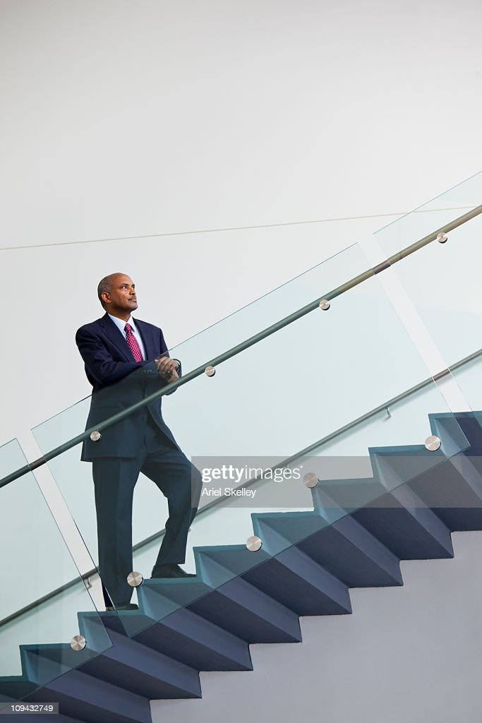African American businessman standing on staircase : Stock Photo
