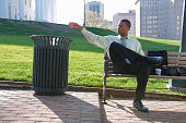 African American businessman throwing trash in garbage can
