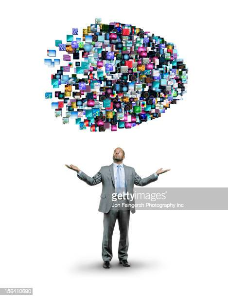 African American businessman underneath cloud of technology images