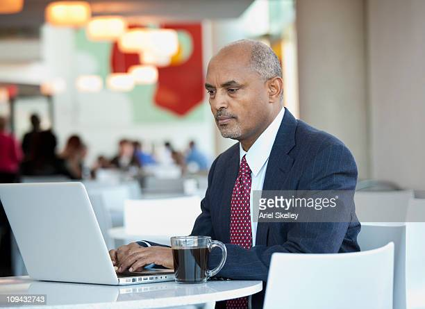 African American businessman using laptop in cafe