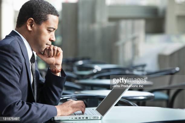 Empresario afroamericano usando una computadora portátil en el cafe