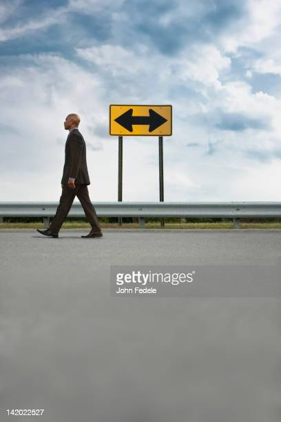 African American businessman walking on road near road sign