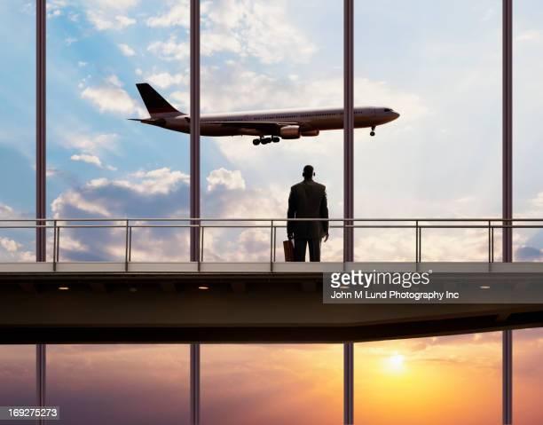 African American businessman watching plane in sky