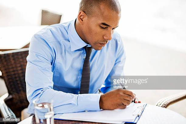 African American businessman writing a document outdoors.