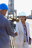African American businesswoman and construction worker shaking hands
