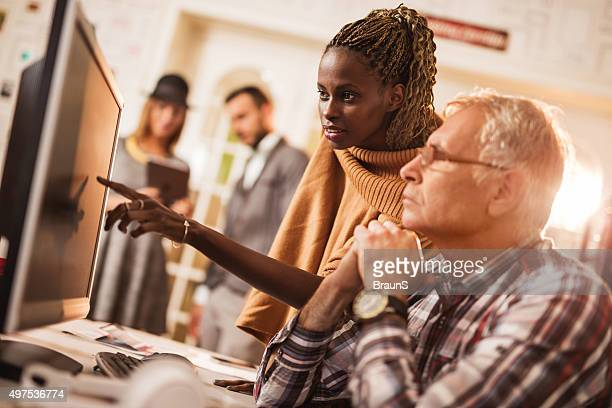 African American businesswoman and mature businessman working on desktop PC.