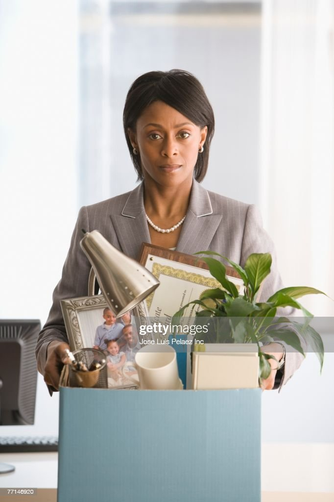 African American businesswoman carrying box of personal items