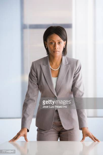 African American businesswoman leaning on table