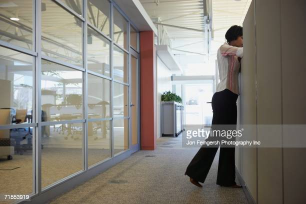 African American businesswoman leaning over cubicle wall