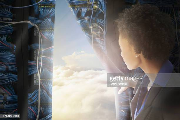 African American businesswoman pulling back curtain to clouds