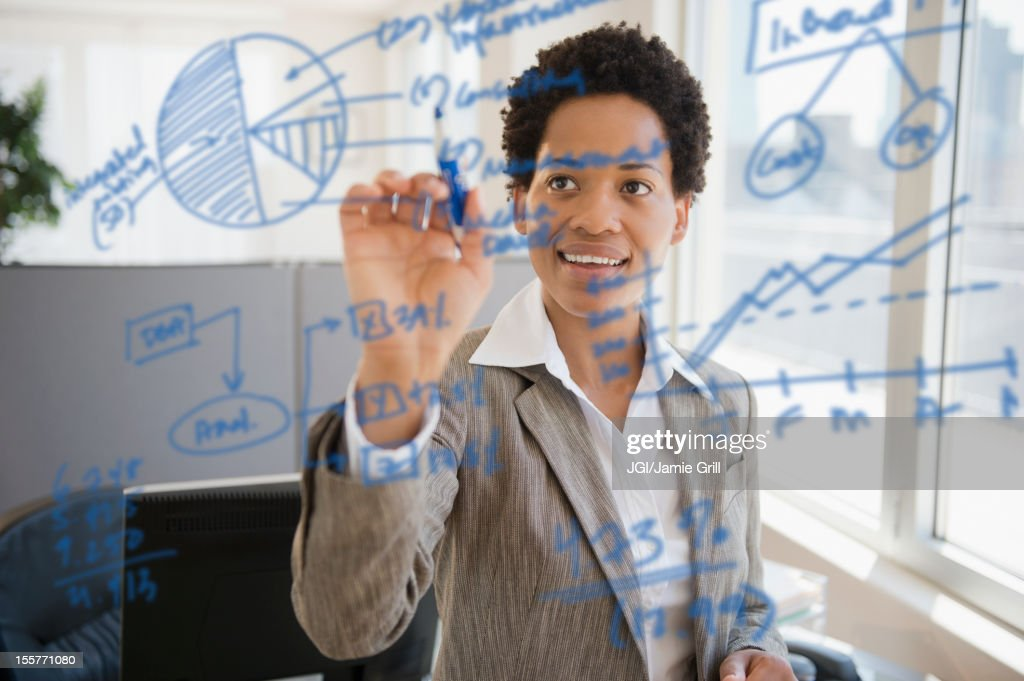 African American businesswoman writing on glass board : Stock Photo